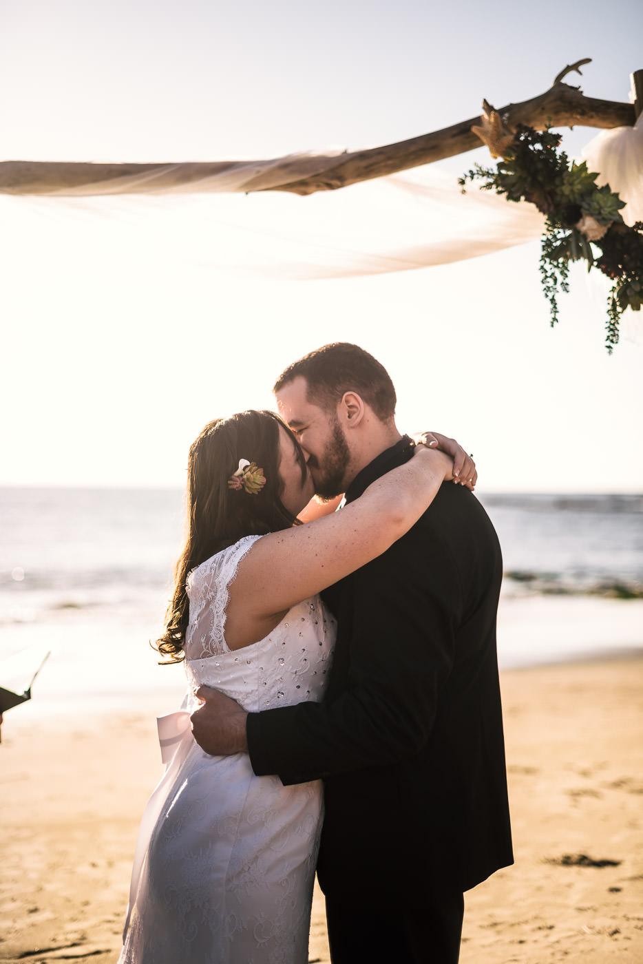 First kiss on the beach with the Pacific Ocean in the bacjground.