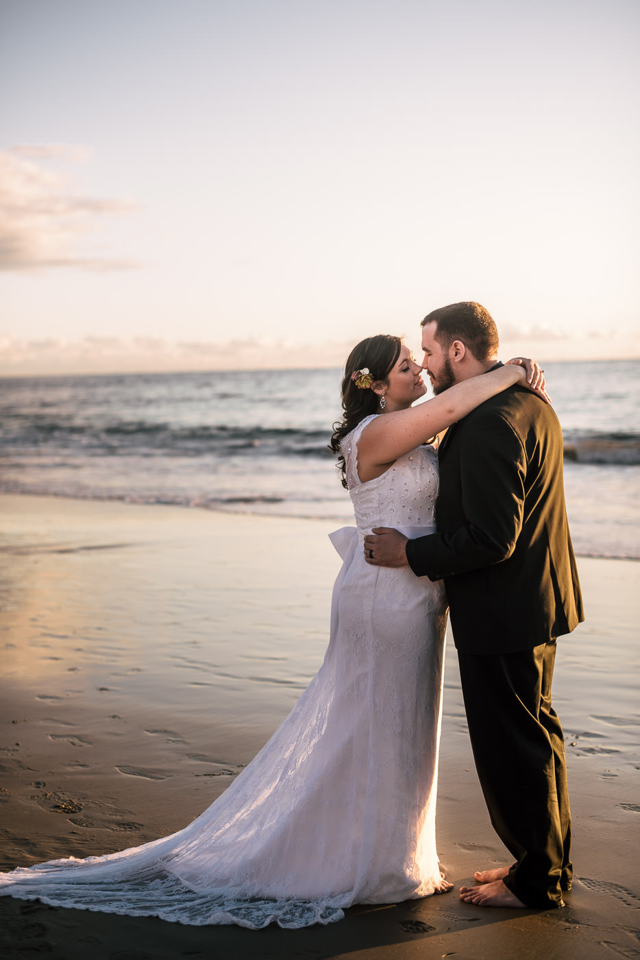 Couple kisses on the wet sand of Laguna Beach at sunset.
