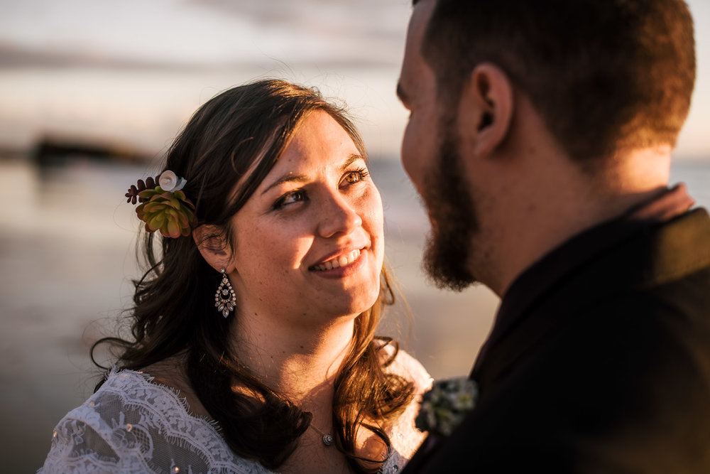 Bride looks deeply into her new husbands eyes as she is bathed in the golden light of sunset.