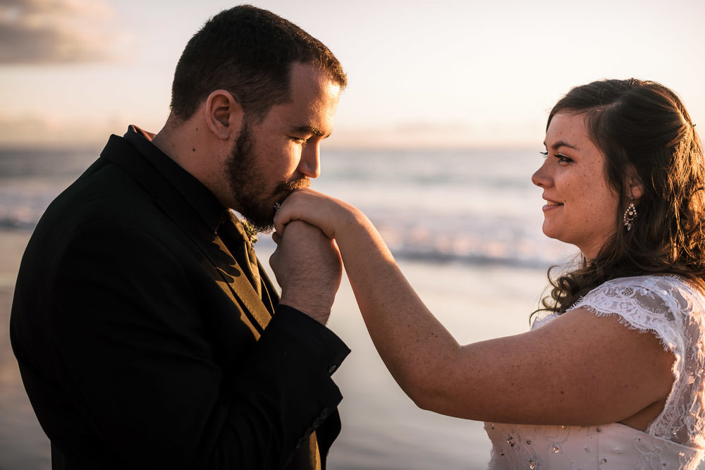 Groom gives the hand of his new wife a kiss as he admires her wedding ring.