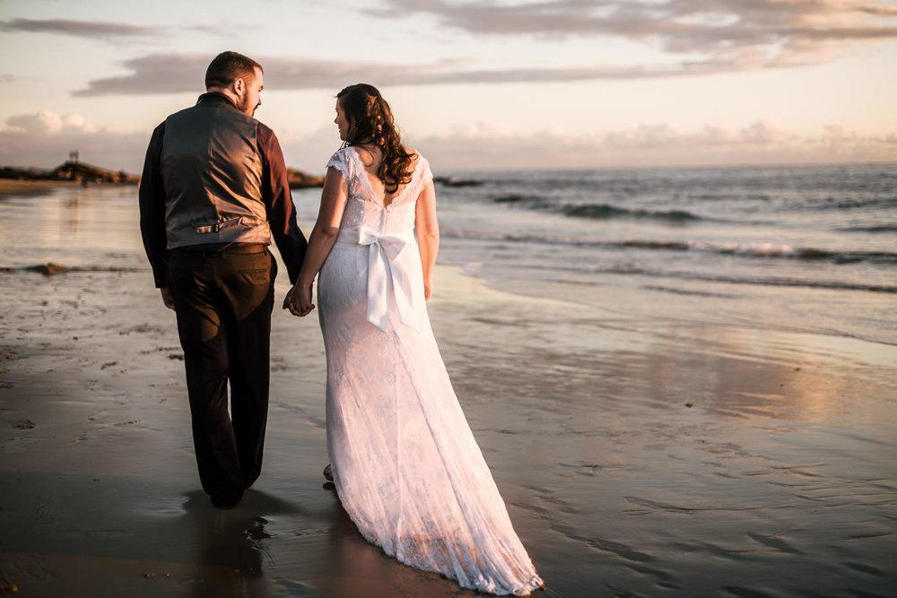 Couple takes a romantic stroll down the beach for their elopement in Laguna Beach.