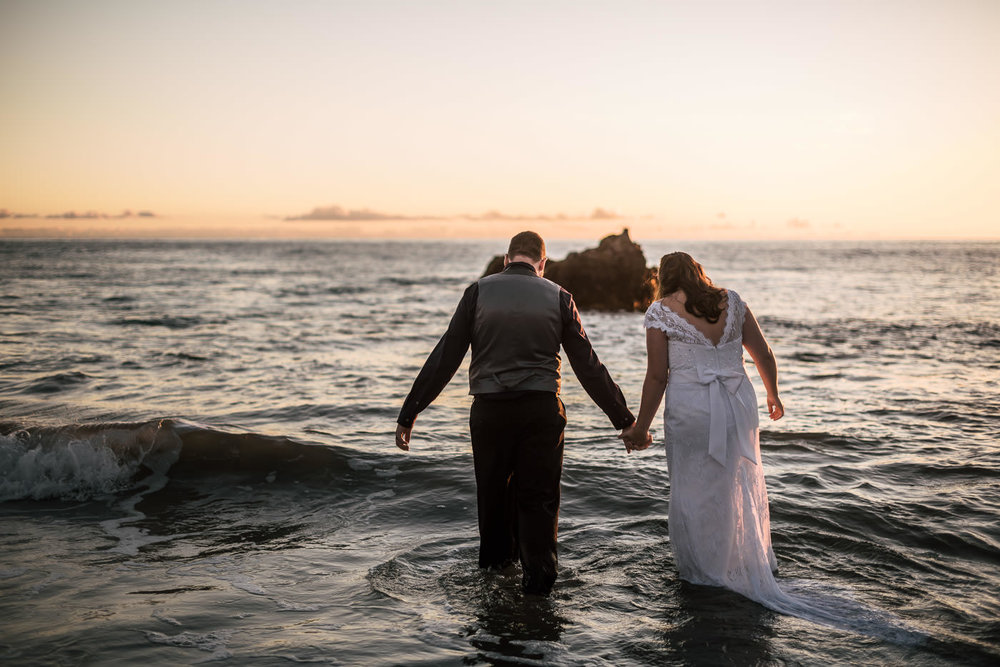 Couple wades into the waves at sunset for a stunning photo session.