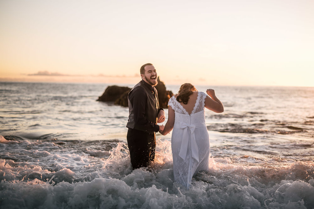 The chilly water makes the bride and groom laugh as the waves crash around them.