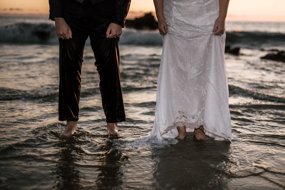 Couple shows off their bare feet as the tide rolls in.