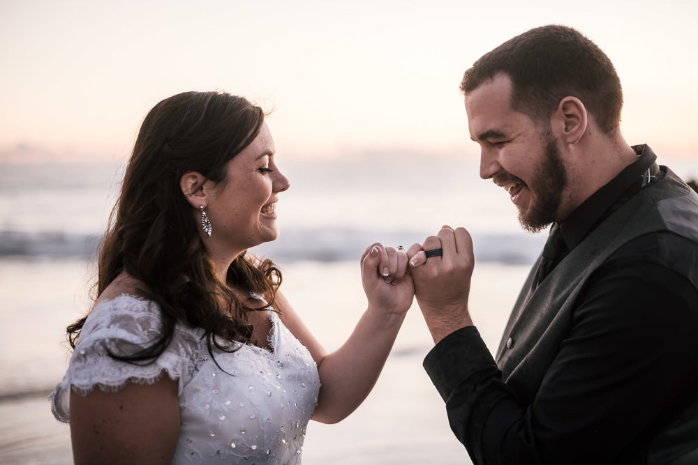 Couple makes a pinky promise at their intimate elopement on the beach.