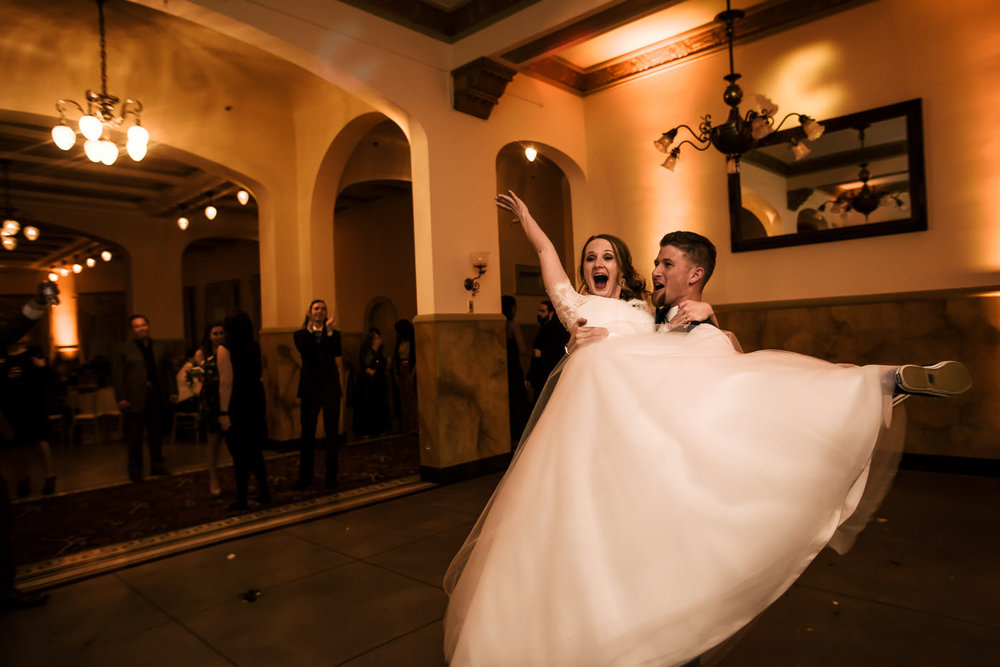 Bride gives a big cheer as her husband twirls her on the dance floor.