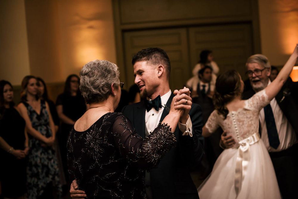 Groom dances with his mother at wedding reception.