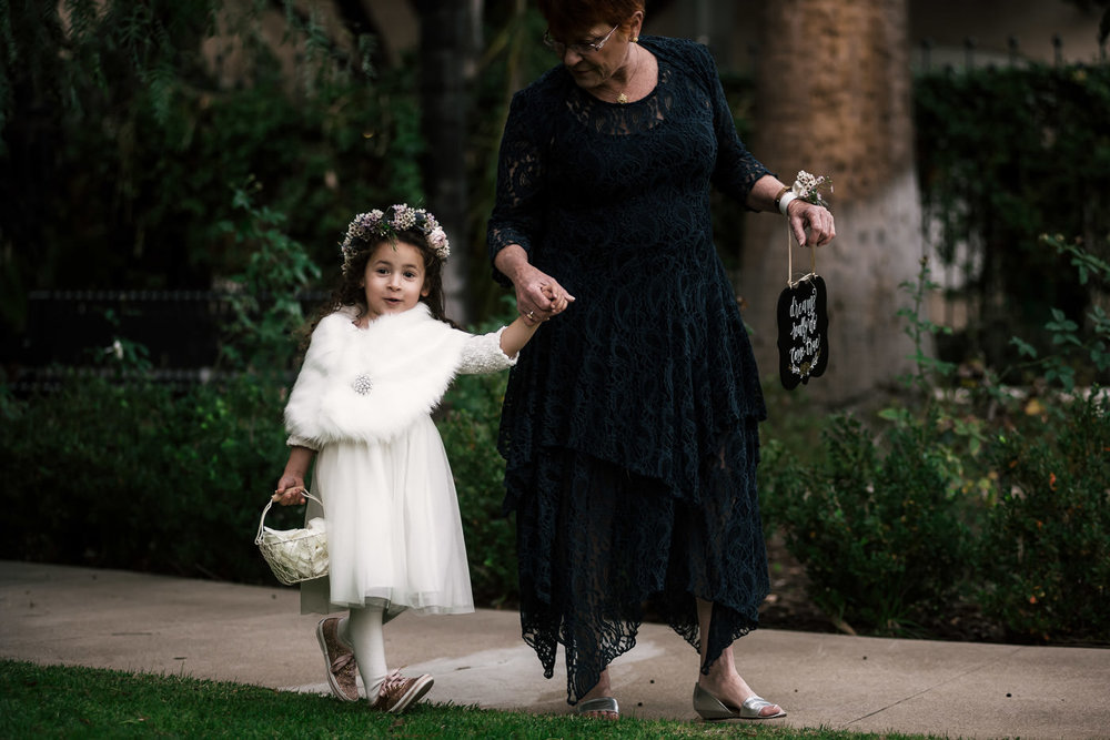 Adorable flower girl with faux fur shawl walks down the asile at Castle Green.