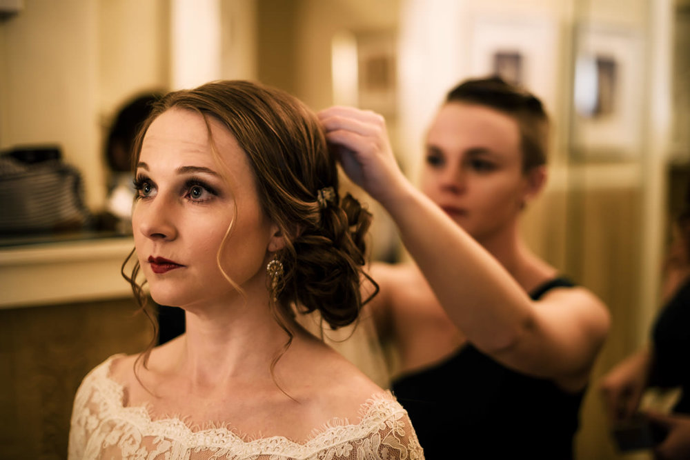 BMaid of Honor puts the finishing touches on brides hair before the wedding.