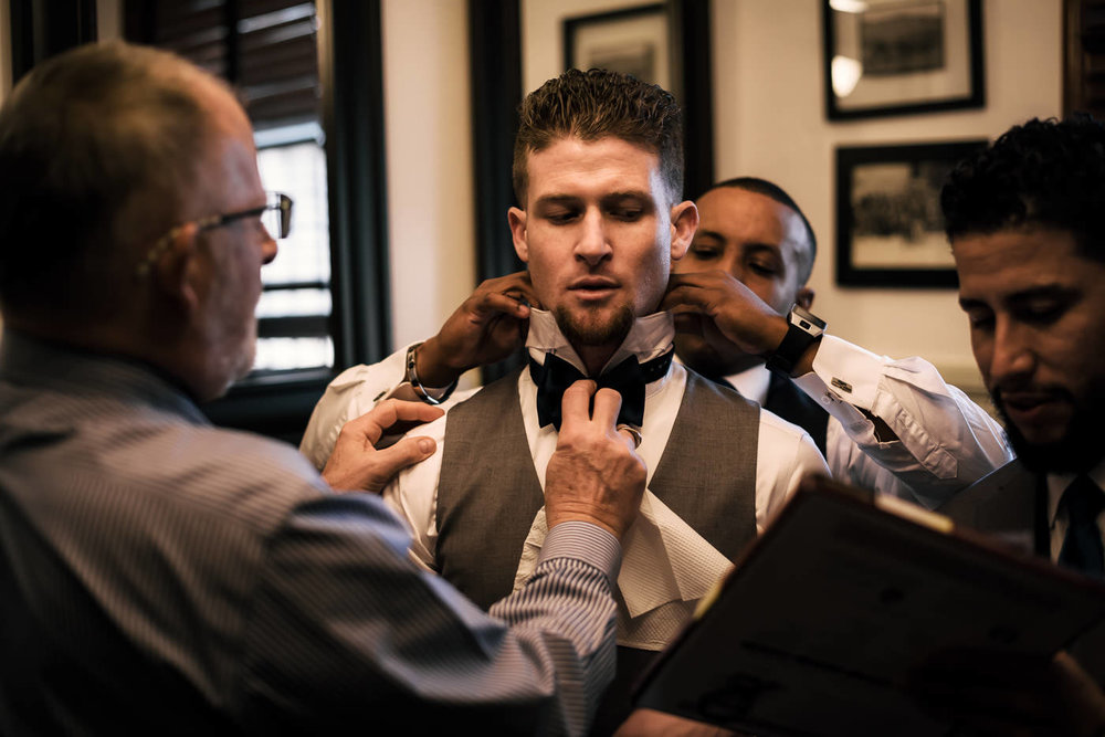 Groomsmen help the groom get ready while he dictates his vows to the best man.