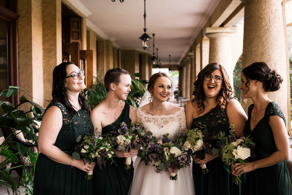 Bridesmaids share a laugh as they pose with the bride before the wedding.