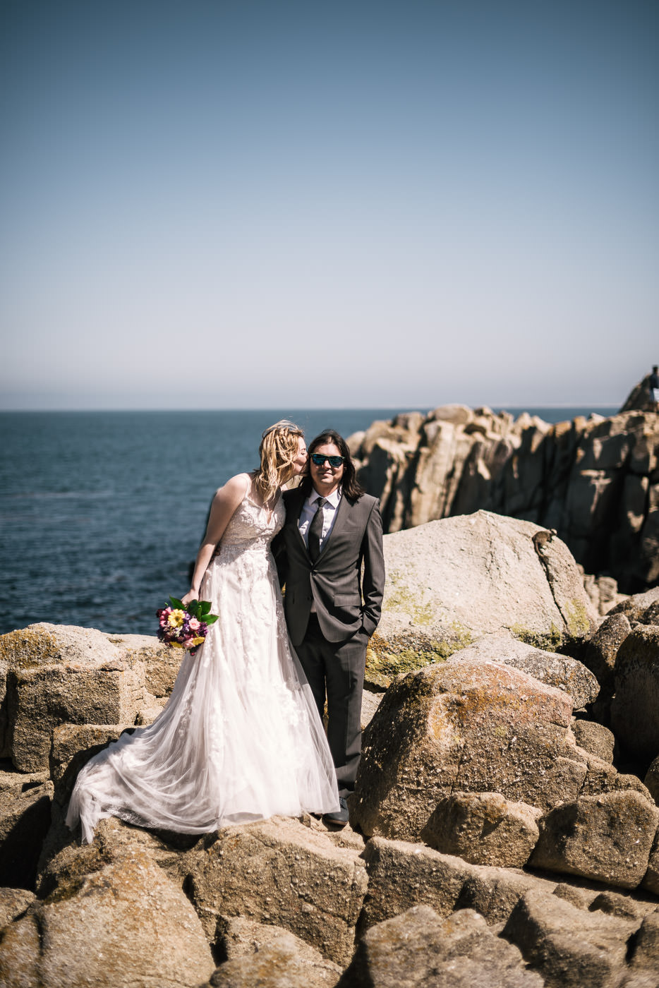 Bride gives the groom a kiss on the rocks of Pacific Grove.