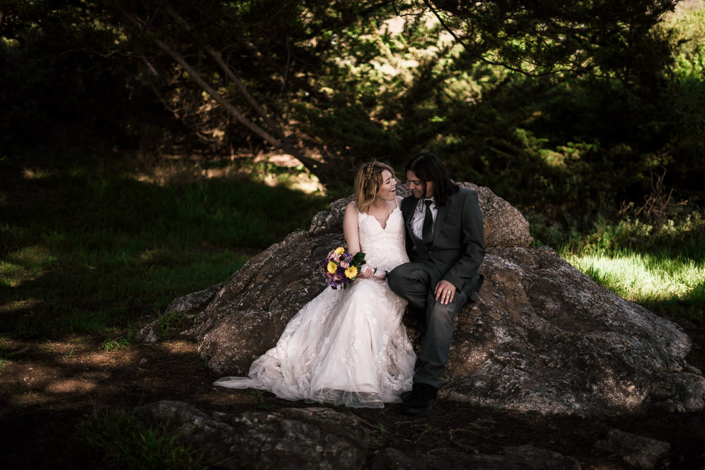 Bride and groom sit for a moment on a large rock under a grove of coastal trees.