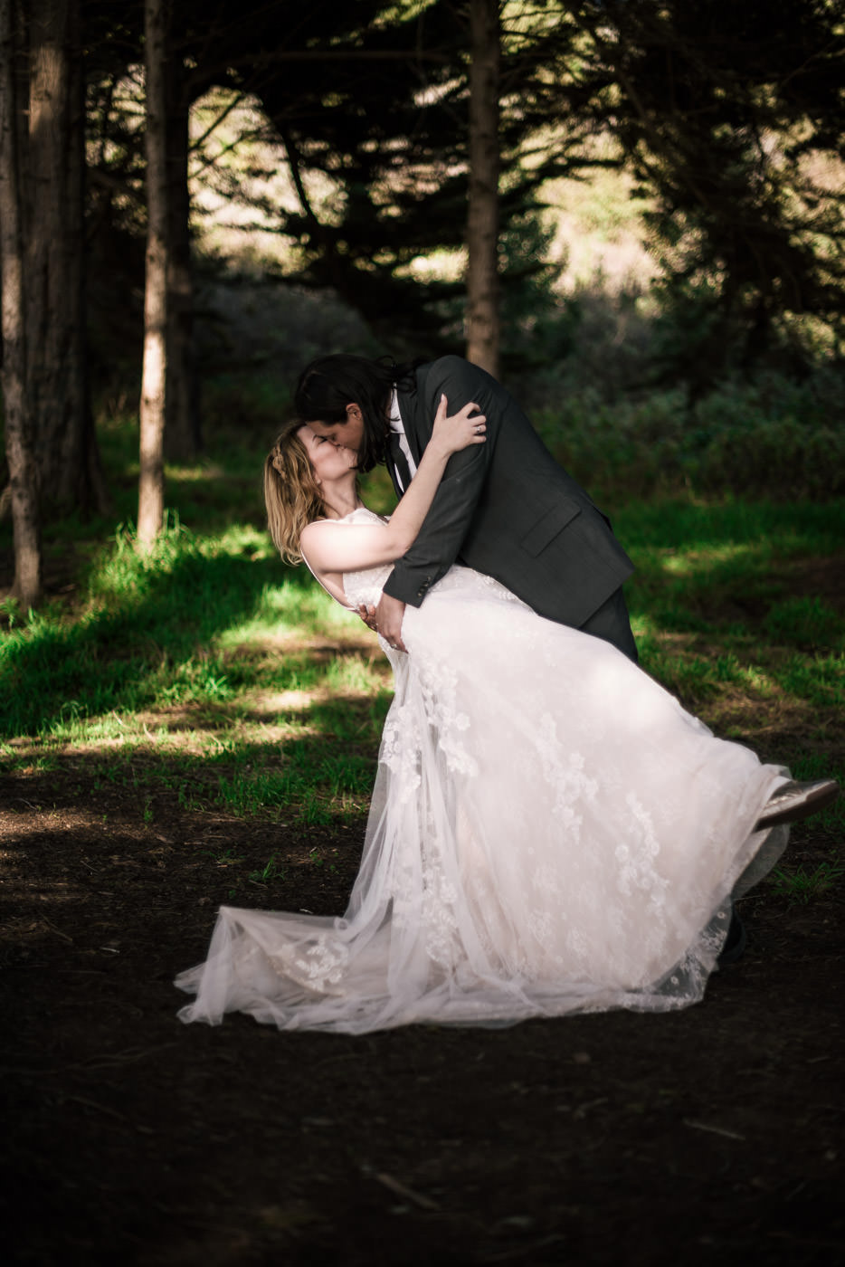 Groom dips his new wife as they dance in the coastal forest of Big Sur.