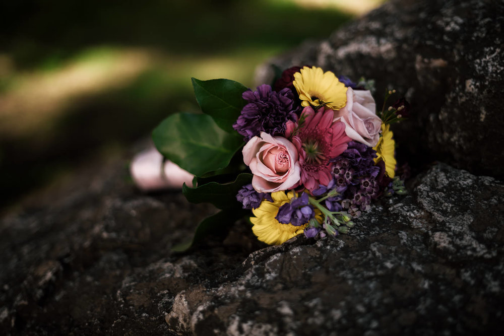 Colorful wedding bouquet sits on a rock .