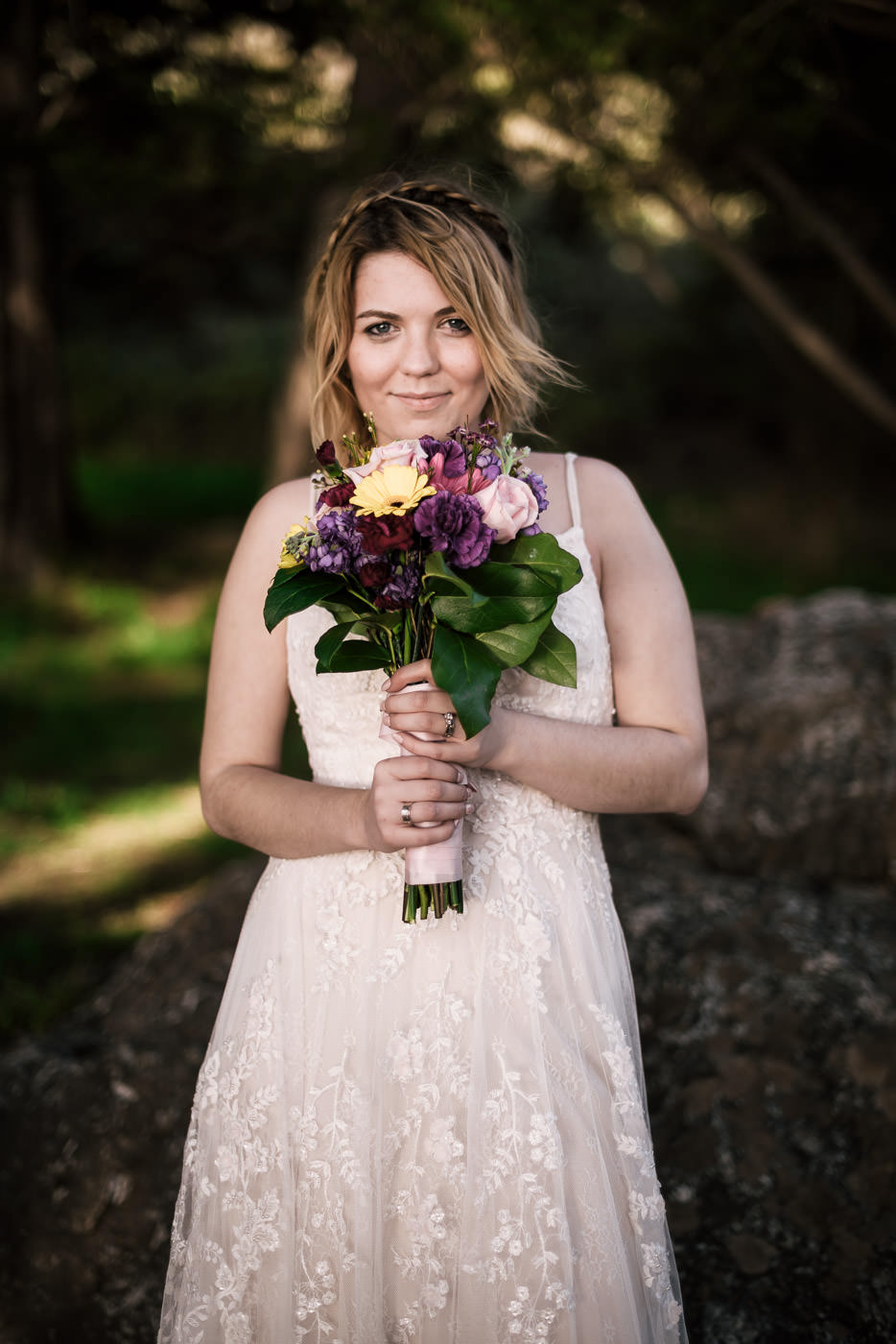 Beautiful bride poses with her wedding bouquet and smiels at the camera.