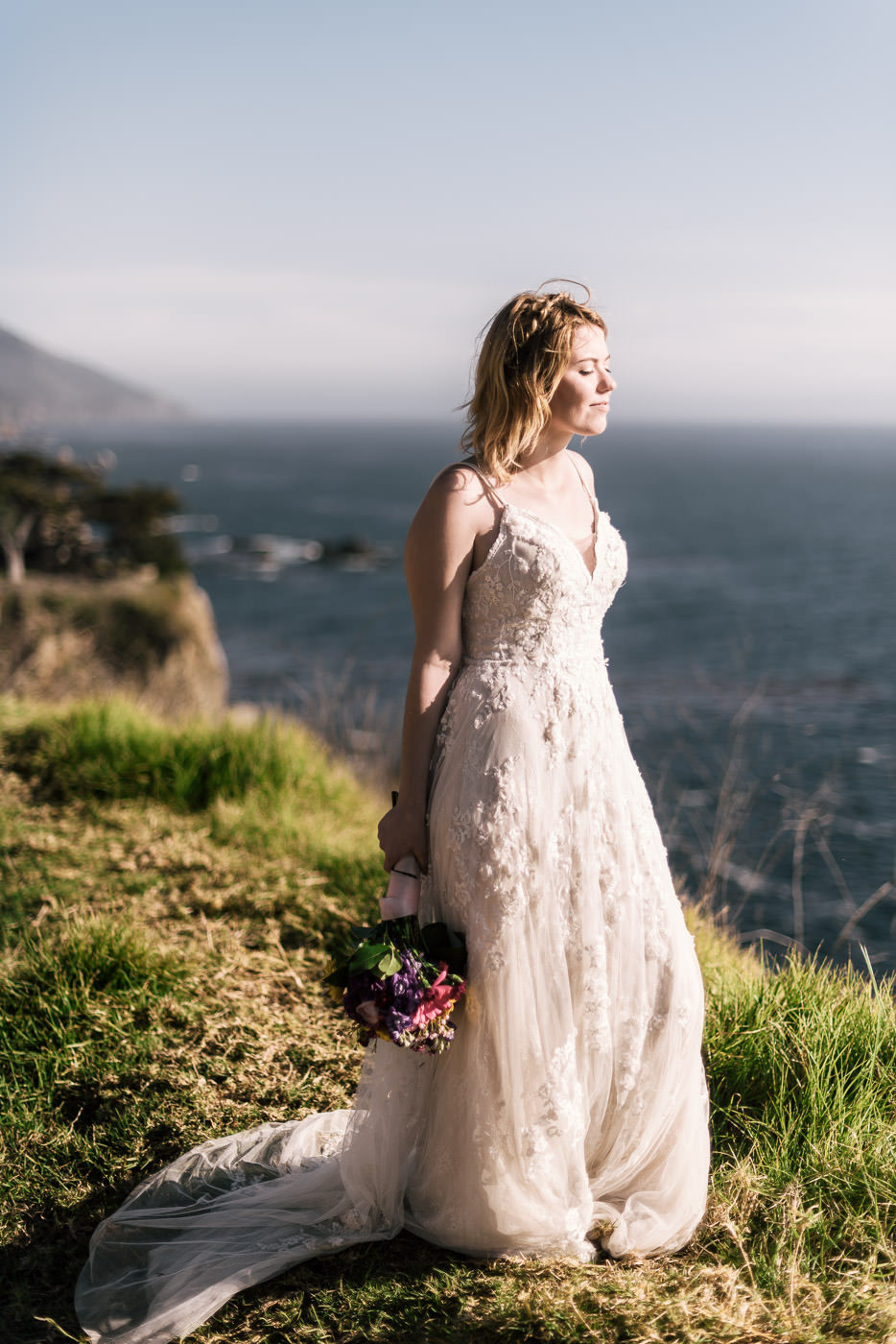 Bride stands on the cliffs of California's unforgettable coastline as the sun sets.