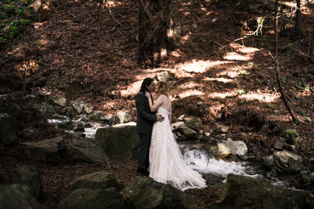 Newlyweds kiss in the forests of California beside a creek.