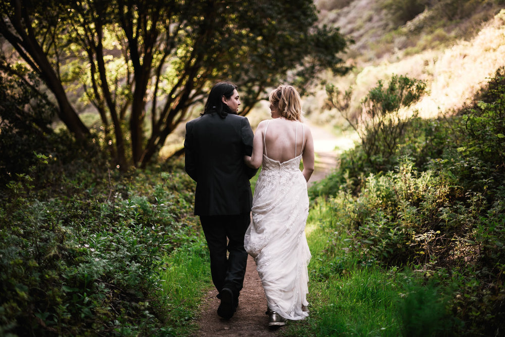 Lovers walk side by side down a hiking path after eloping.
