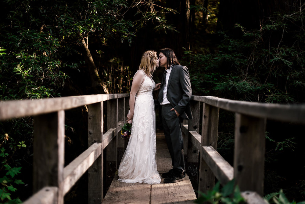 Tender kiss on an old wooden bridge spanning a creek after eloping in Monteray.