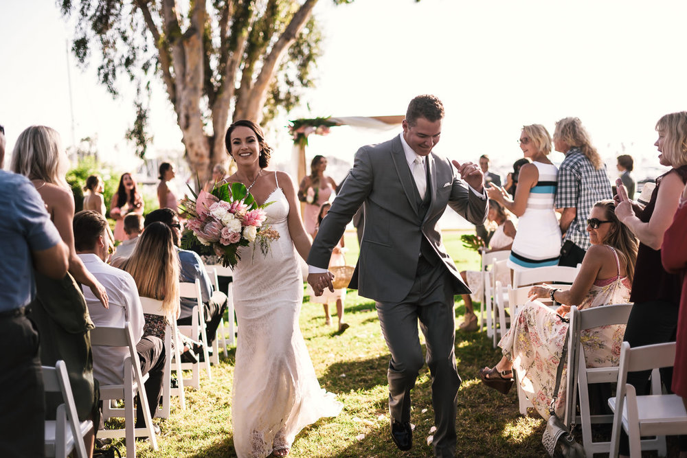 Groom dances down the aisle with his new bride in her beautiful dress and carrying a gorgeous bouquet.
