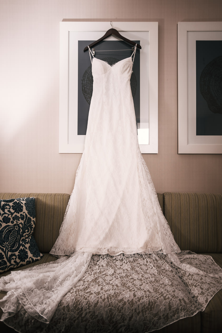 Beautiful white wedding dress hangs from a picture frame in the Brides hotel room.