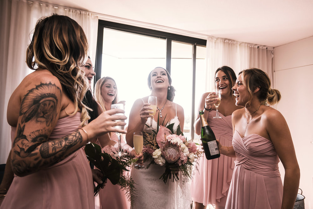 Bride toasts with her bridesmaids as they prepare to hed to the ceremony.