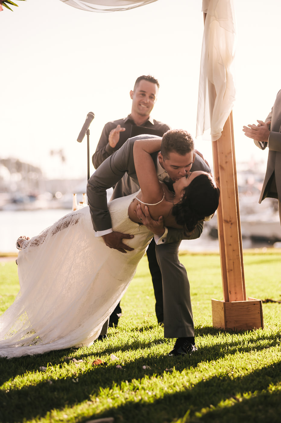 Groom dips his new wife during their first kiss at Marina VIllage.