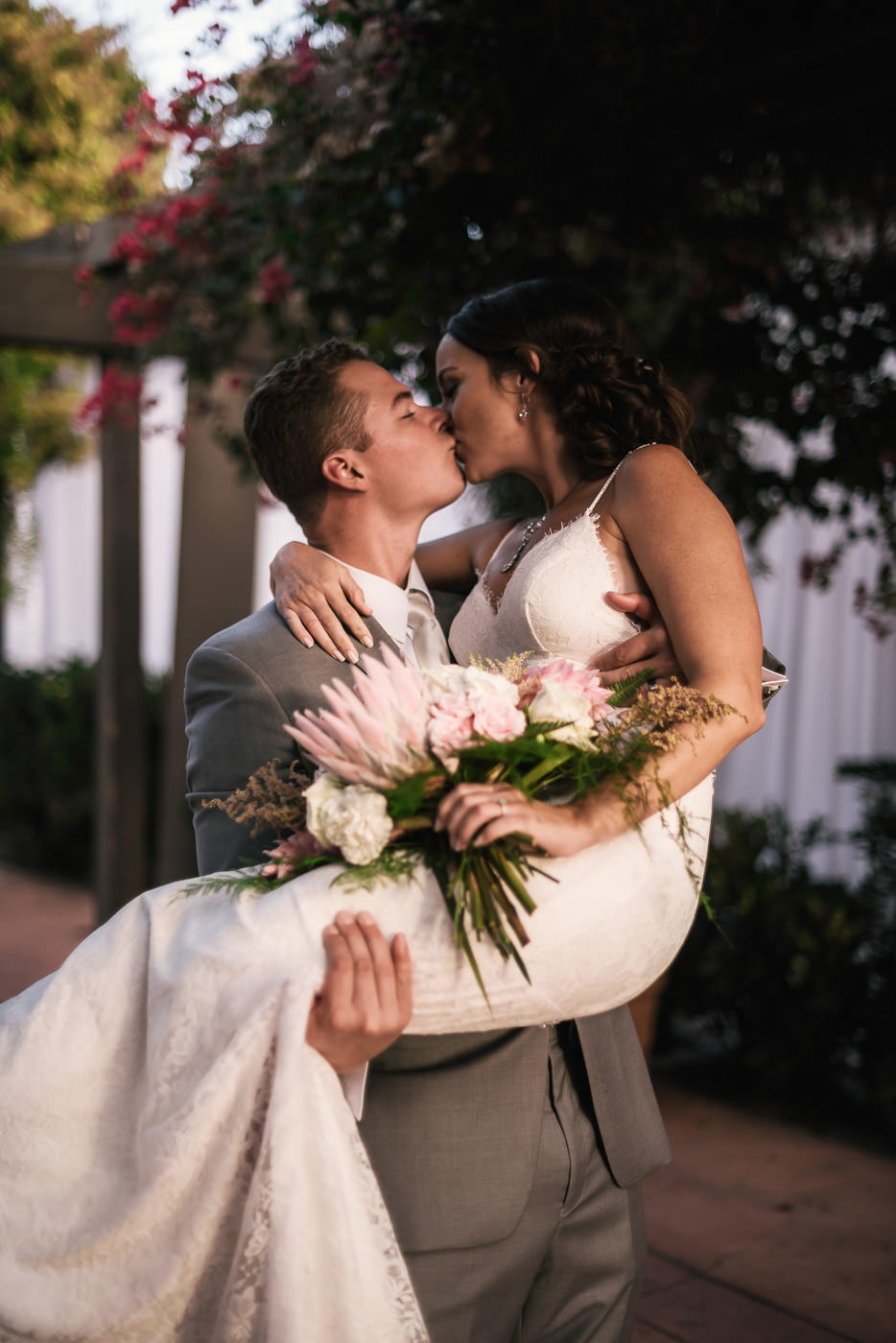 Groom lifts bride to carry her into the reception but stops to give her a romantic kiss at their Marina Village wedding in San Diego.