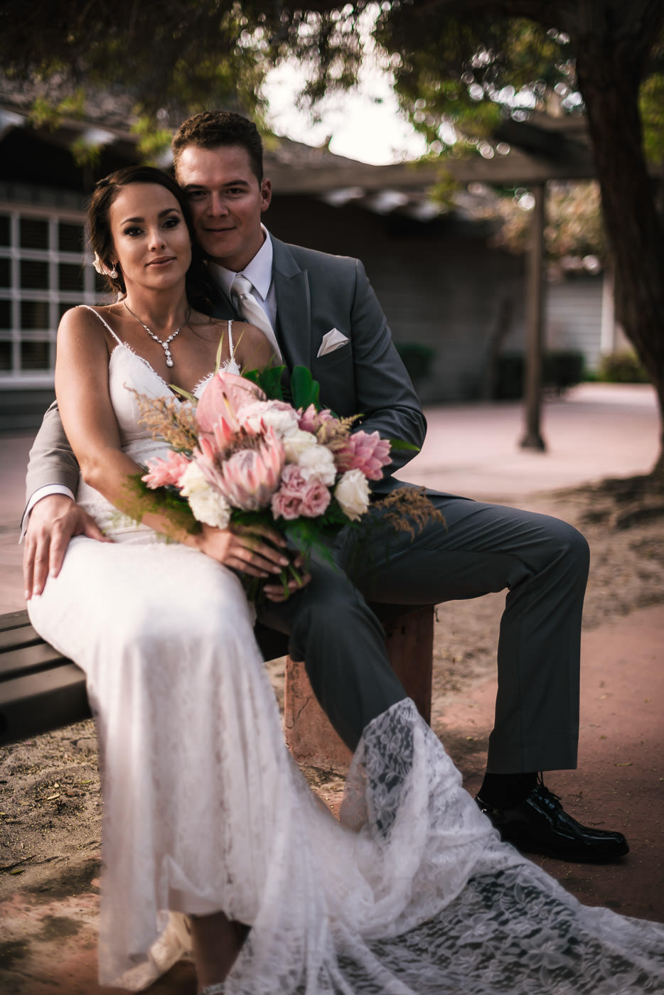 Beautiful newlyweds sit on a bench and pose for a timeless portrait.