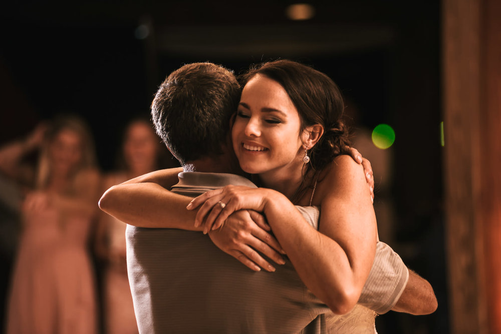 Daughter hugs her father after a sweet dance.