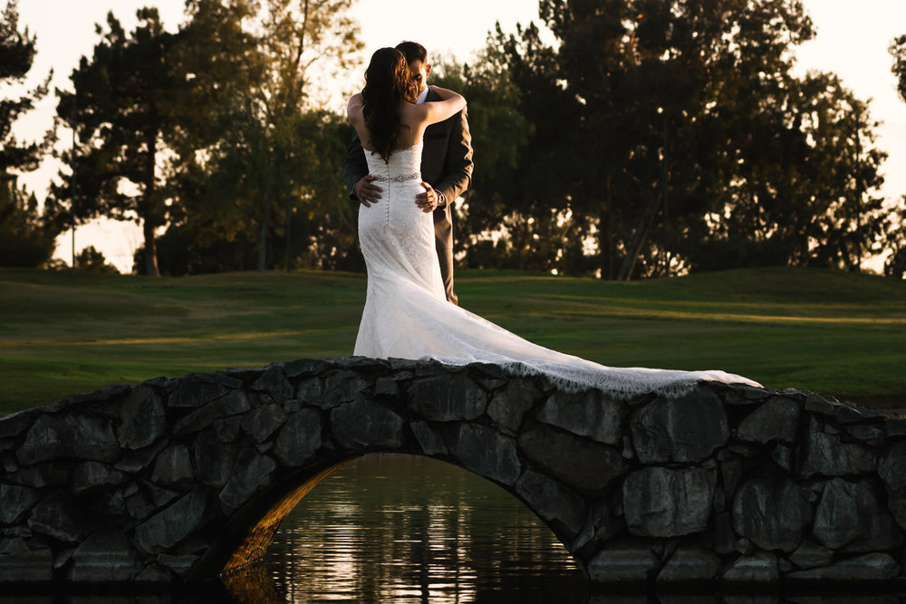 Newlyweds stand atop a beautiful stone bridge over a pond at the Alta Vista Country Club in Placentia.