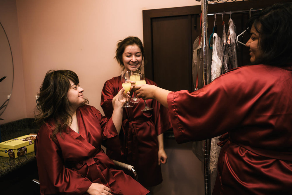 Three bridesmaids say cheers and have a drink while getting ready for the big day.
