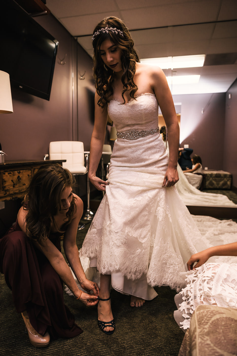 Maid of Honor helps the bride with her heels.