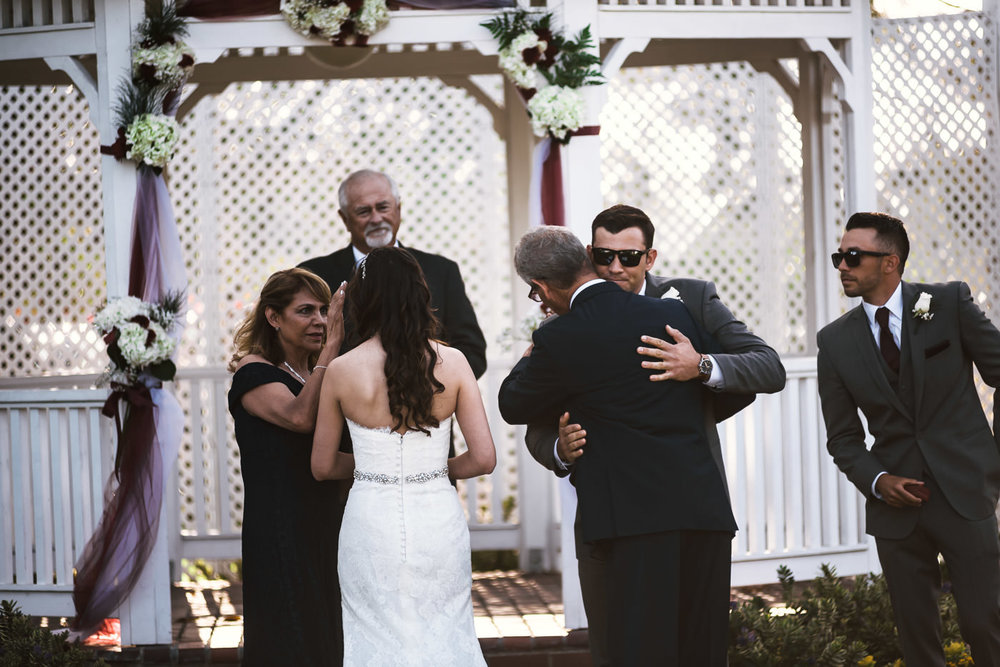 Groom gives his father in law a big hug before the wedding ceremony.
