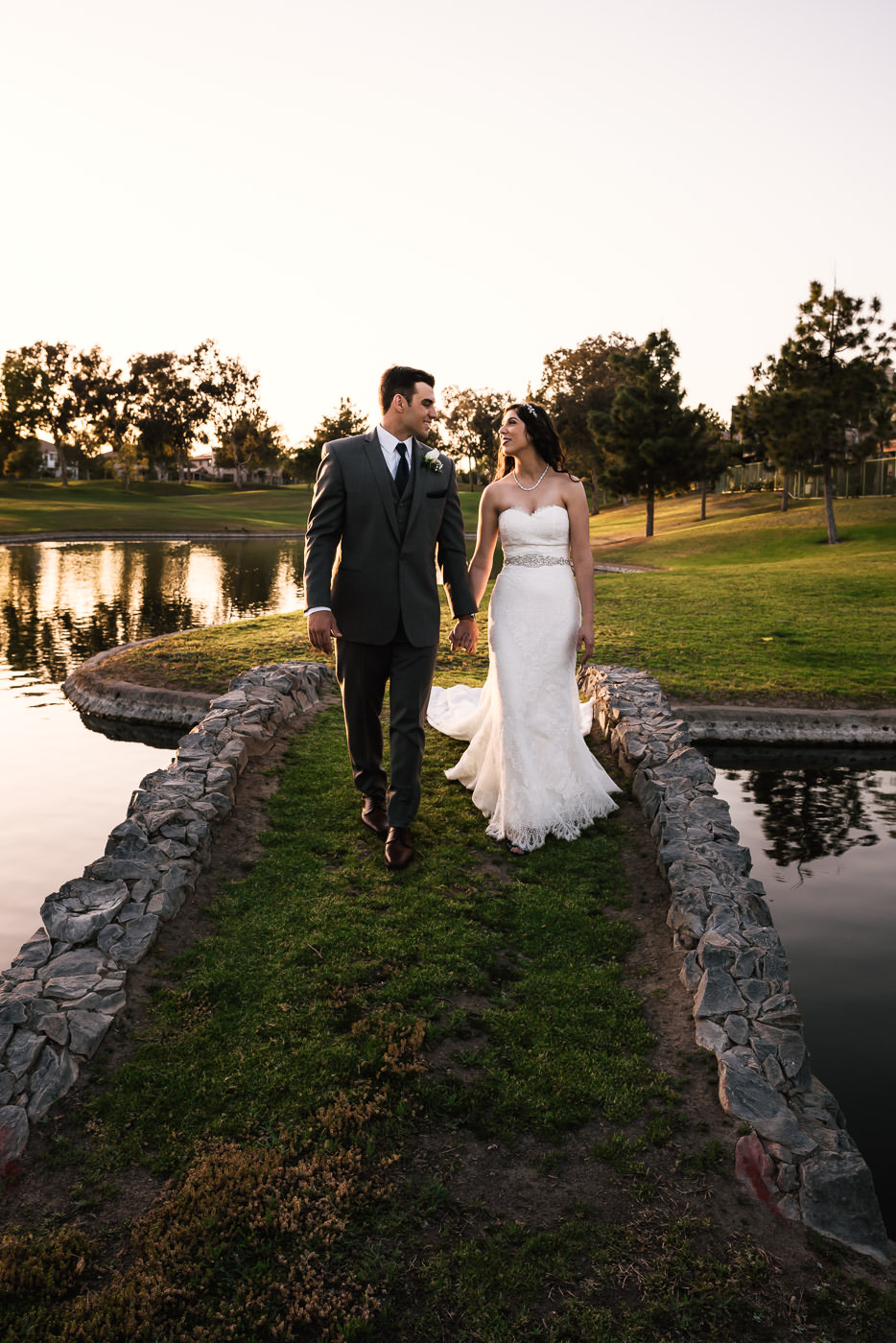 Newly married couple walks hand in hand across the stone bridge spanning the pond.