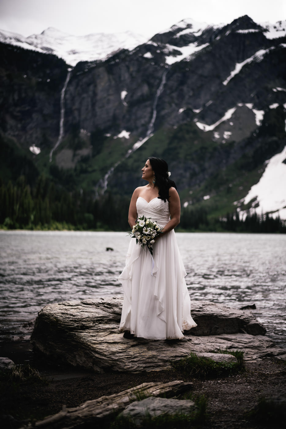 Bride stands on the shores of Avalanche lake in Glacier National Park after her marriage ceremony.