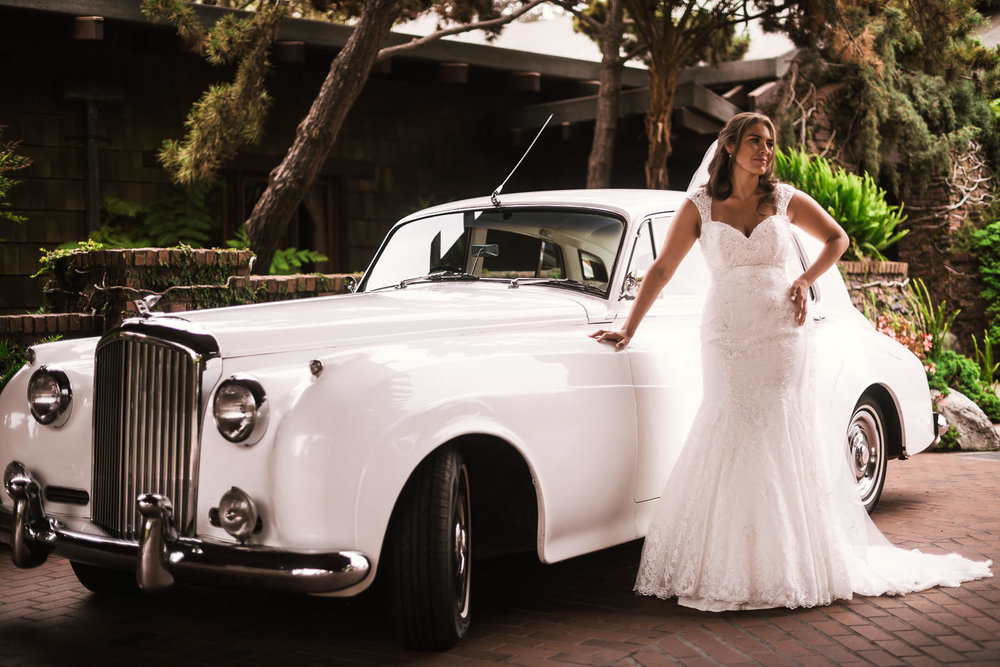 Beautiful bride poses with a classic Rolls Royce before taking it to her wedding.