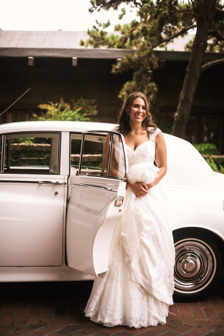 Brides leans up against the classic Rolls Royce that has arrived to take her to the wedding.