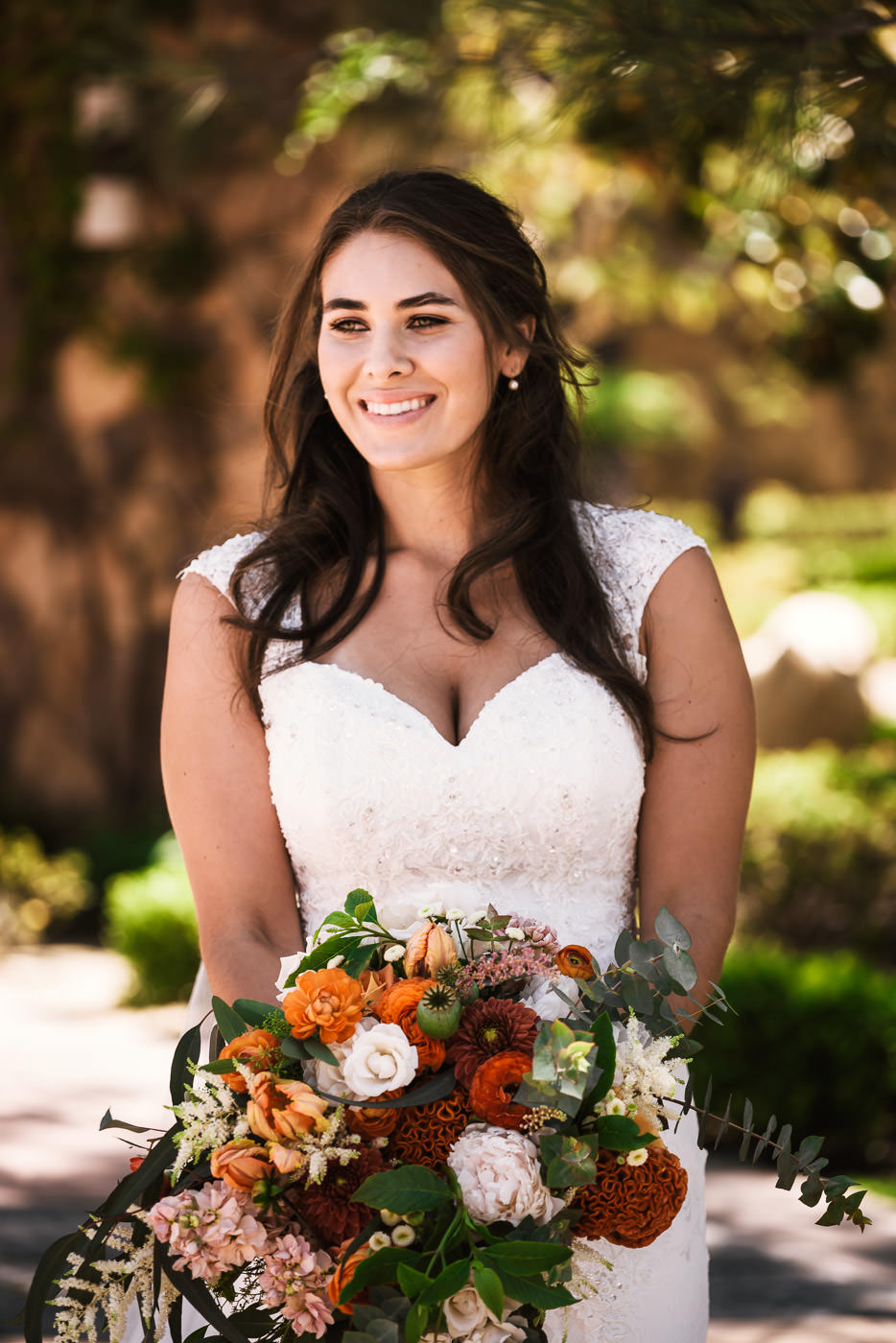 Soon to be married bride smiles as she holds her beautiful fall colored bouquet.