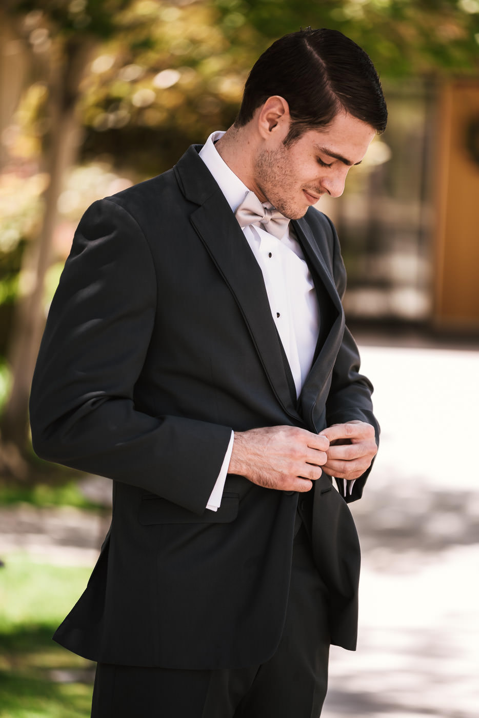 Groom buttons his jacket as he prepares to head to the chapel.