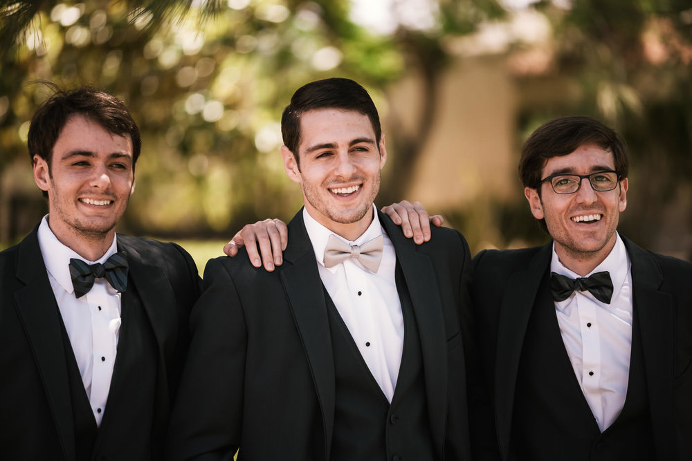 Groomsmen laugh with the groom before the big event.