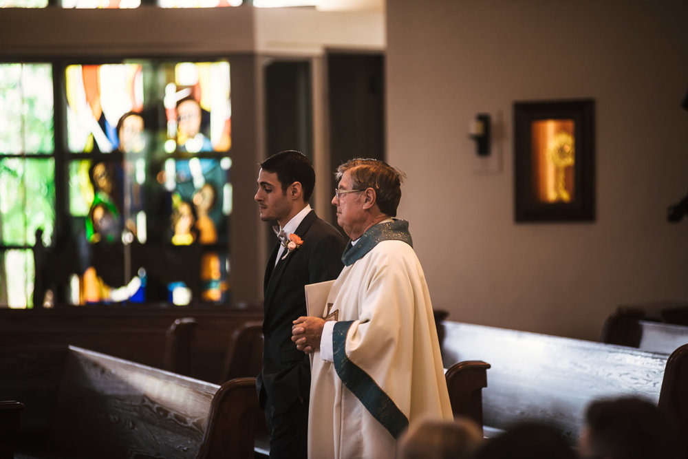 Groom walks with his priest down the aisle at the cathedral for their marriage ceremony.