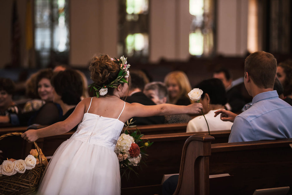 Flower girl hands out roses as she heads down the aisle.