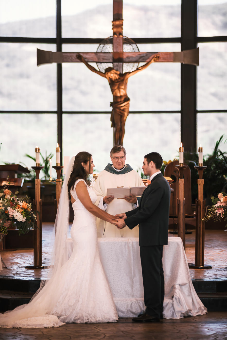 Bride and groom hold hands during the marriage ceremony and say their vows.
