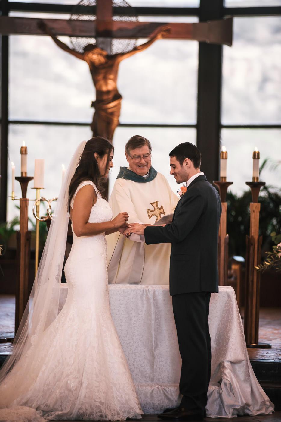Bride puts wedding ring on her new husbands finger.