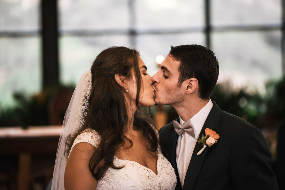 Romantic kiss between newlyweds at their St Therese Carmel Church wedding.