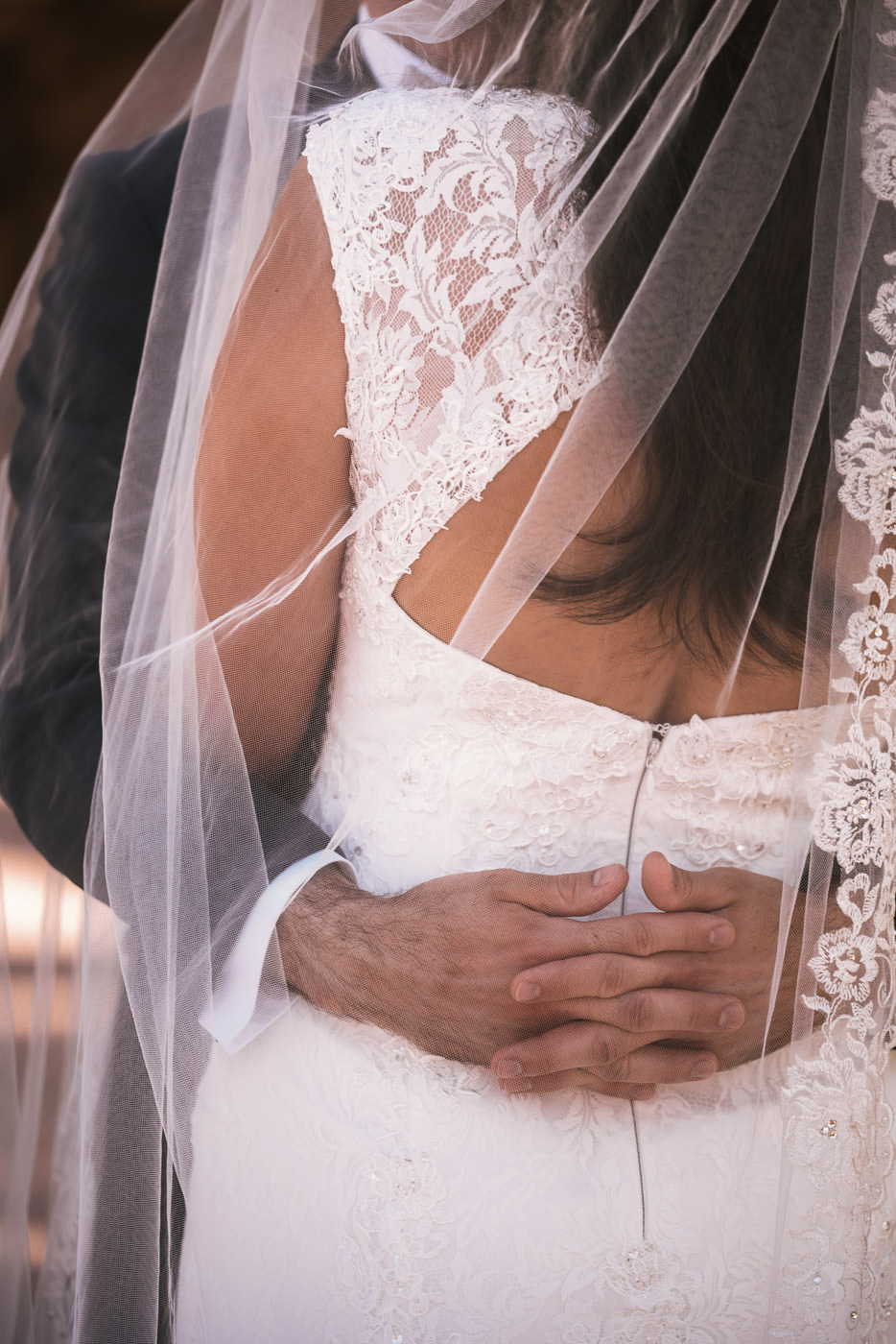 Husband clasps his arms around his bride and holds her romantically.