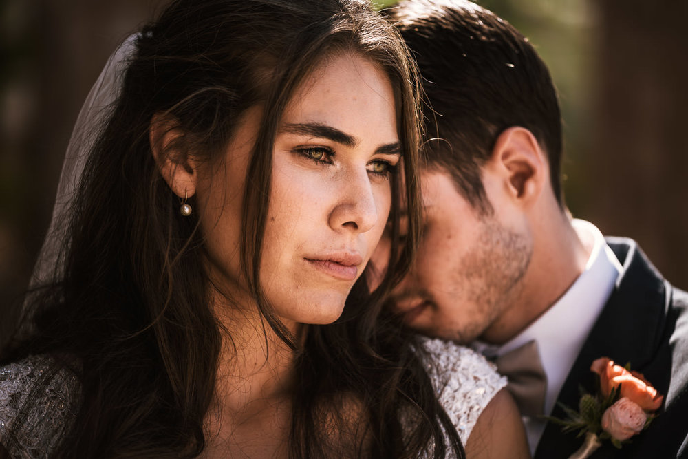 Groom rests his head on his beautiful bride for a romantic wedding photo in San Diego.