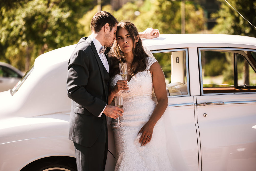 Couple toasts their new marriage with glasses of champagne in front of a classic Rolls Royce.